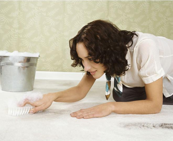 Девушка чистит палас щеткой и пеной