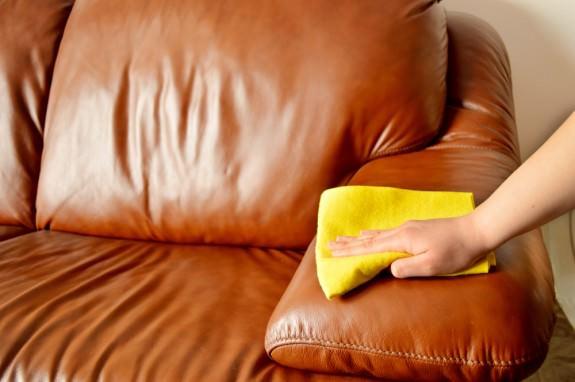Девушка протирает пыль с кожаного дивана