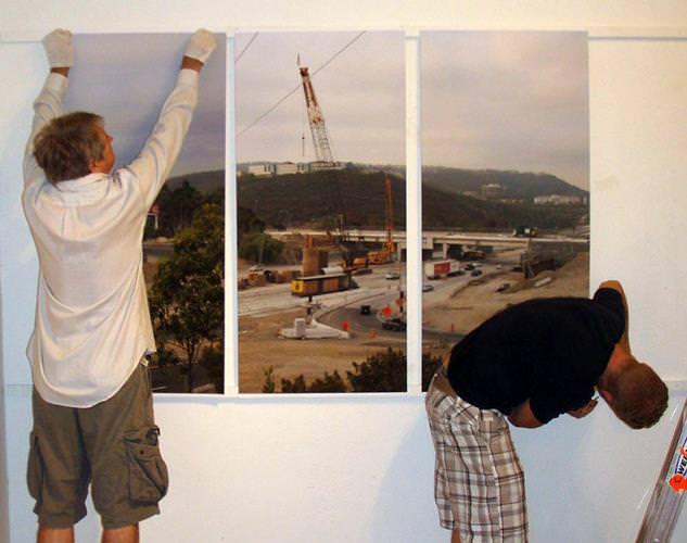 Мужчины вешают картины на стену