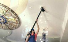 Девушка моет натяжные потолки специальным пылесосом