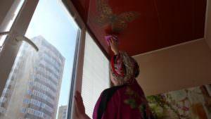 Женщина моет потолок