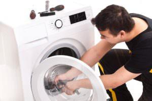 Мужчина ремонтирует стиральную машину