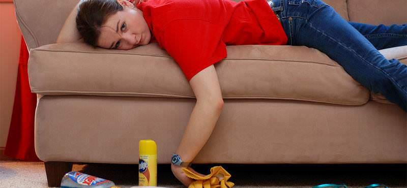 Уставшая женщина лежит на диване