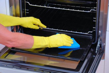Протирают духовку тряпкой в перчатках