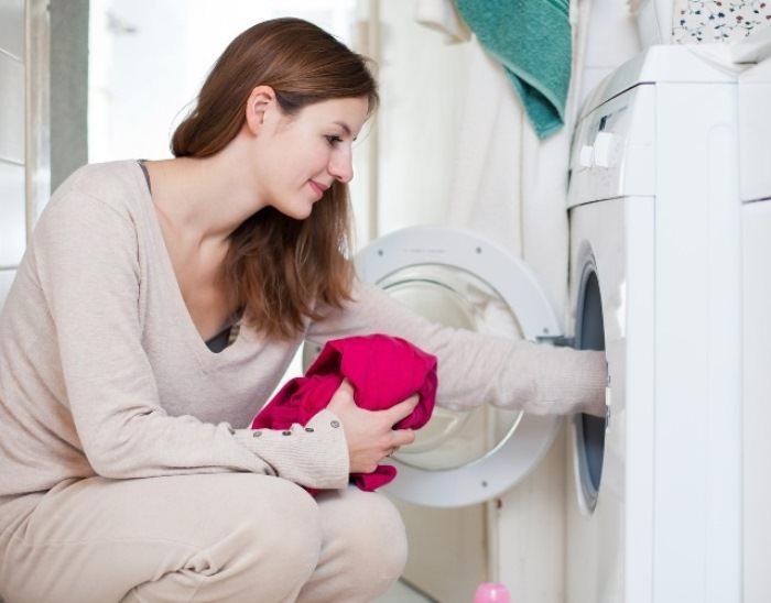 Девушка кладет пальто в машинку