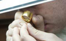 Эксперт смотрит золото через лупу