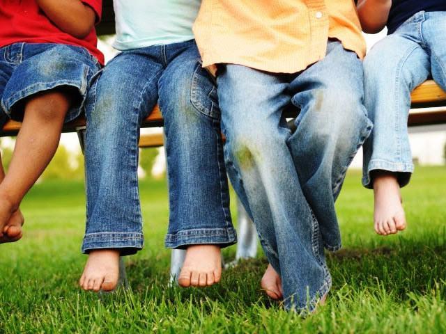 Дети с пятнами от травы на джинсах