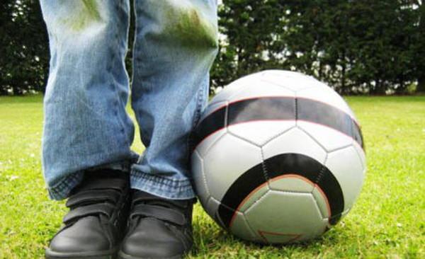 Мальчик в грязных джинсах рядом с мячом