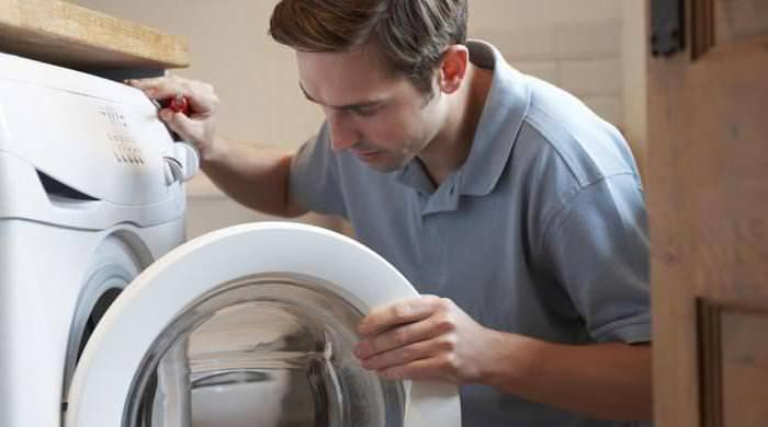Мужчина смотрит в открытую дверь стиральной машины