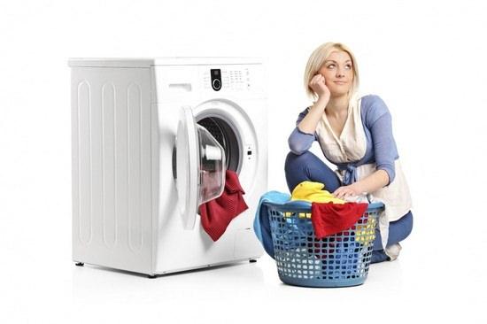 Девушка в раздумьи около стиральной машины