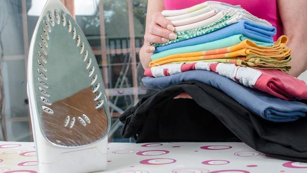 Утюг и стопка одежды