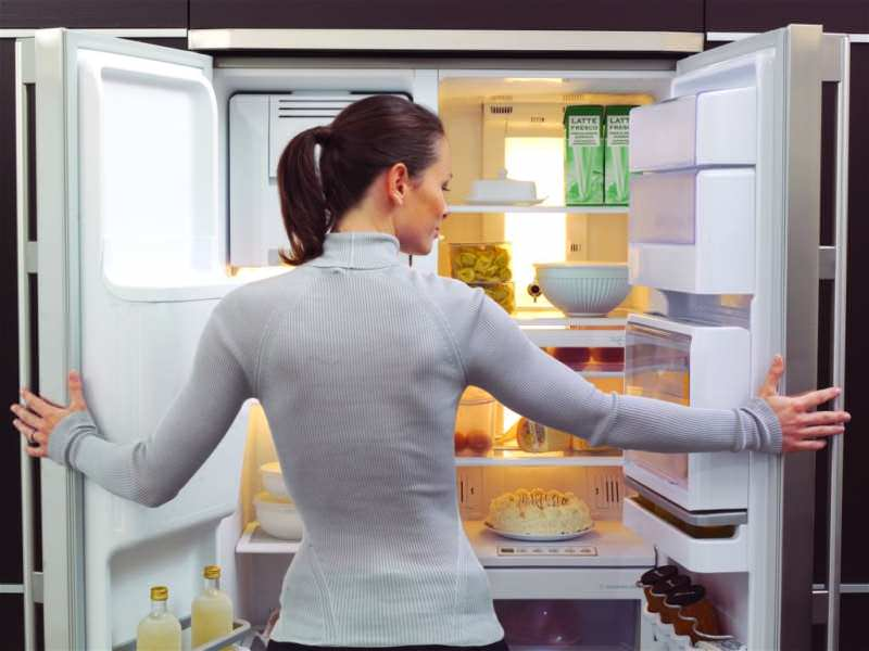 Девушка у открытого холодильника